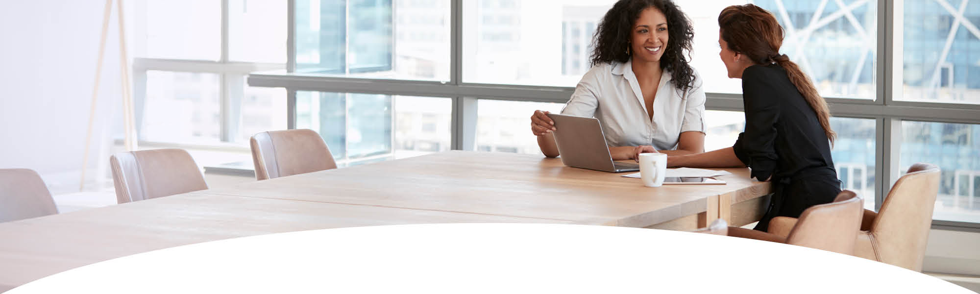 Get Help - two women sitting in front of a computer at a conference table
